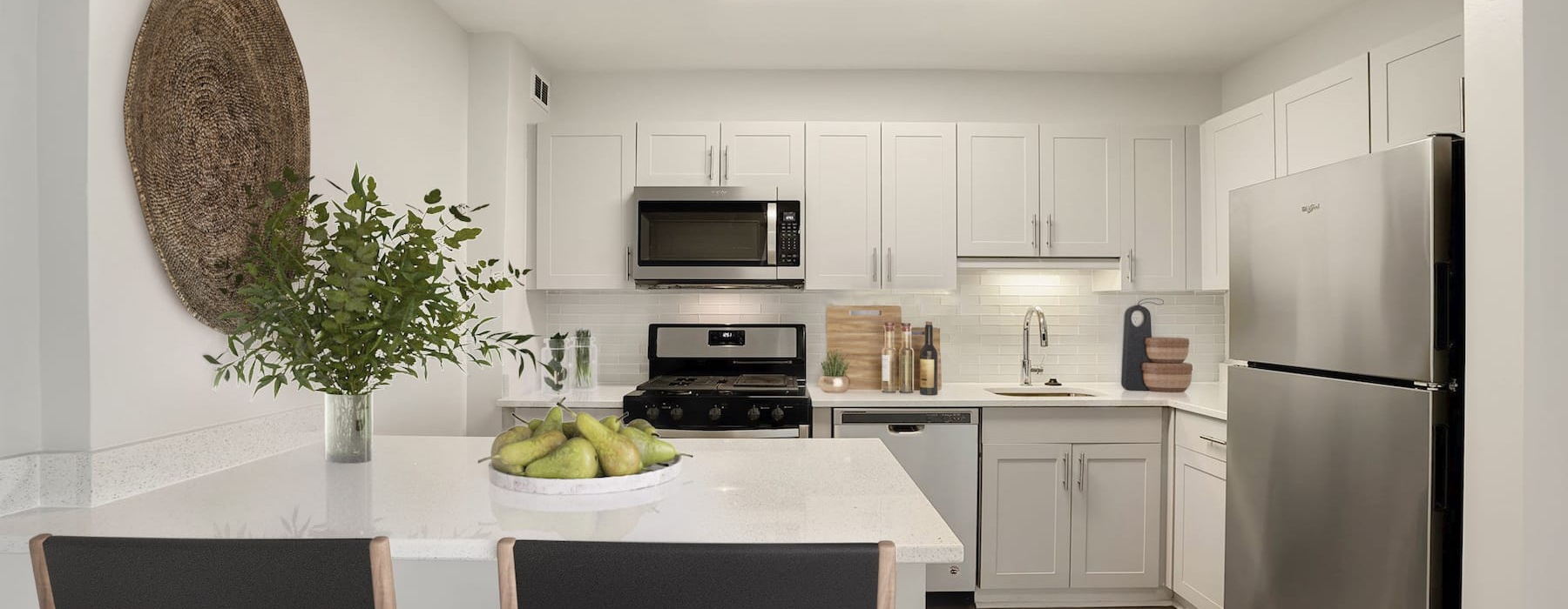 Luxury, furnished kitchen with tile backboard, island dining table with counter seating, and stainless steel appliances